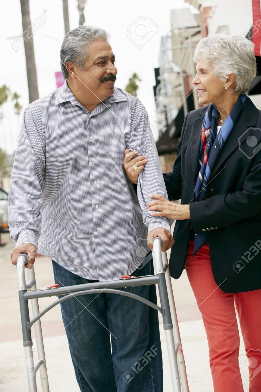 Wife Helping Senior Husband To Use Walking Frame Stock Photo