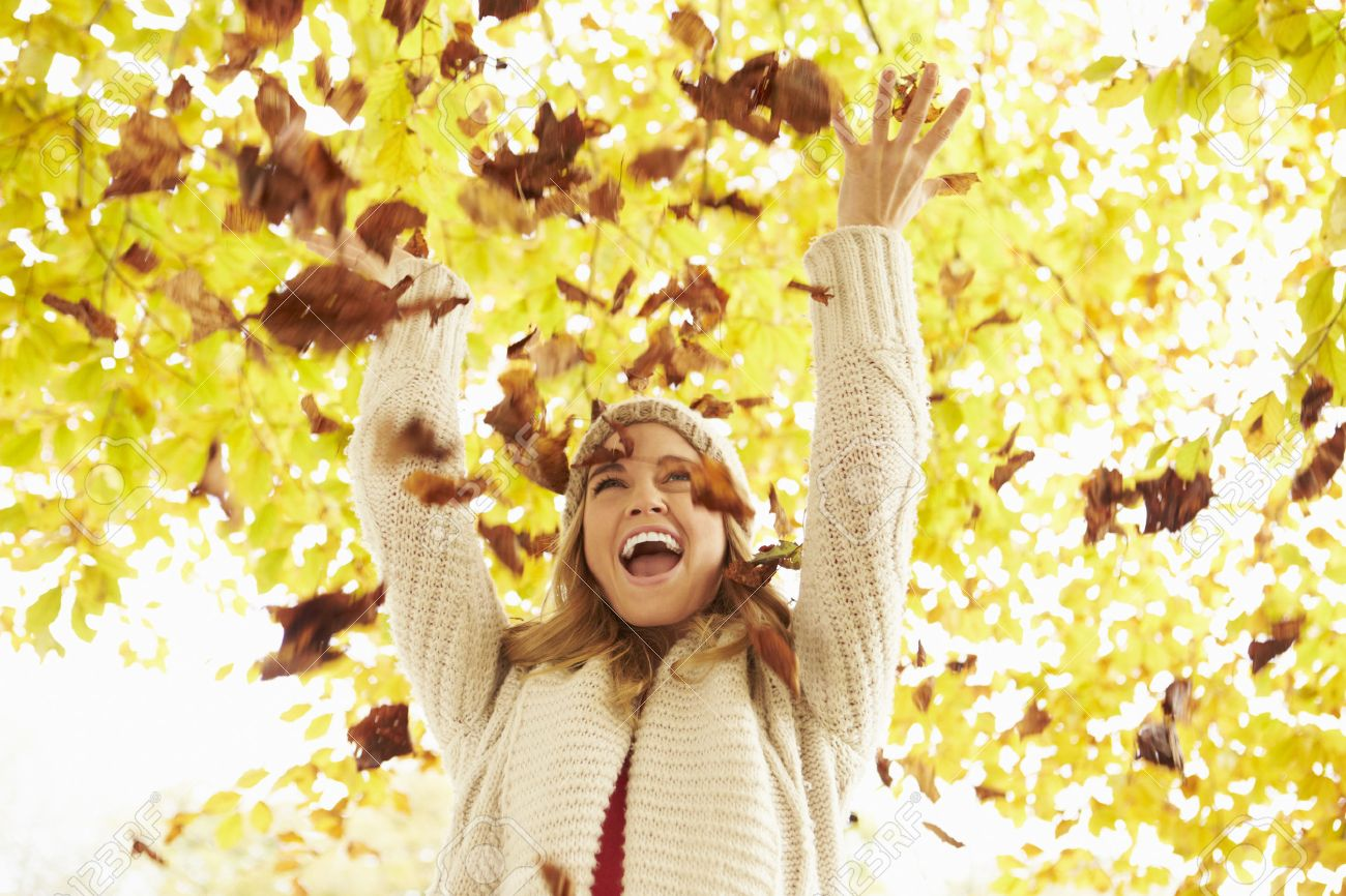 Woman Throwing Autumn Leaves Into The Air Stock Photo - 42270012