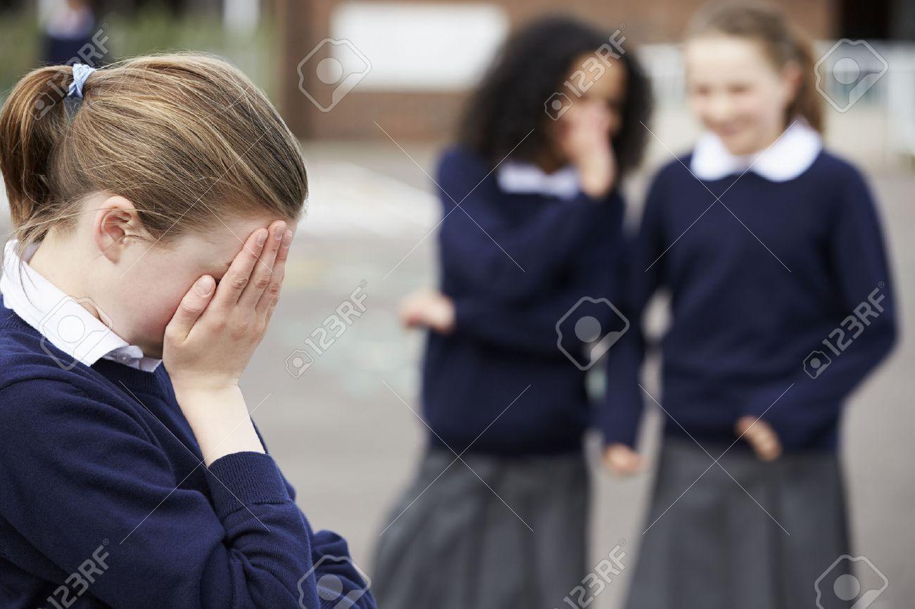 Female Elementary School Pupils Whispering In Playground Stock Photo - 42401925