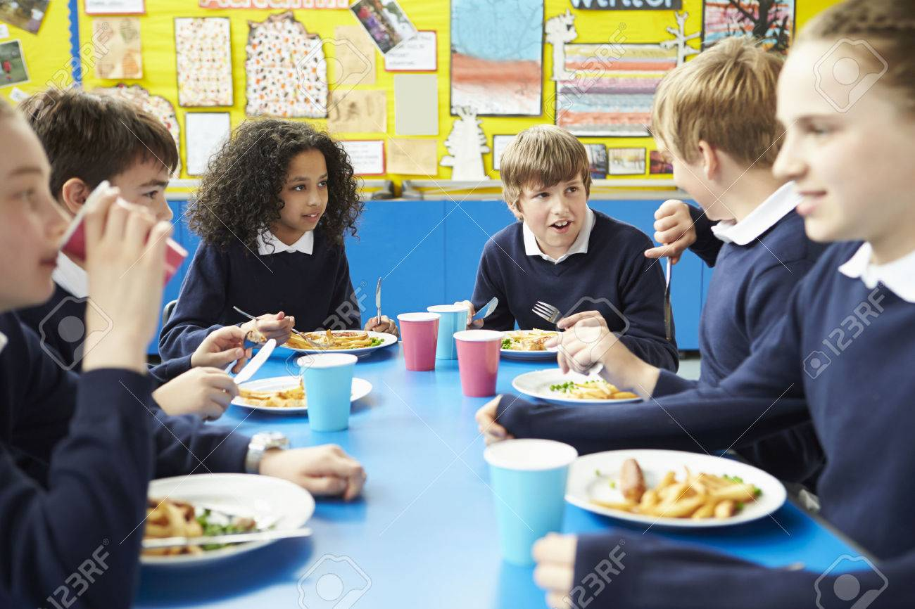 Schoolchildren Sitting At Table Eating Cooked Lunch Stock Photo - 42401961