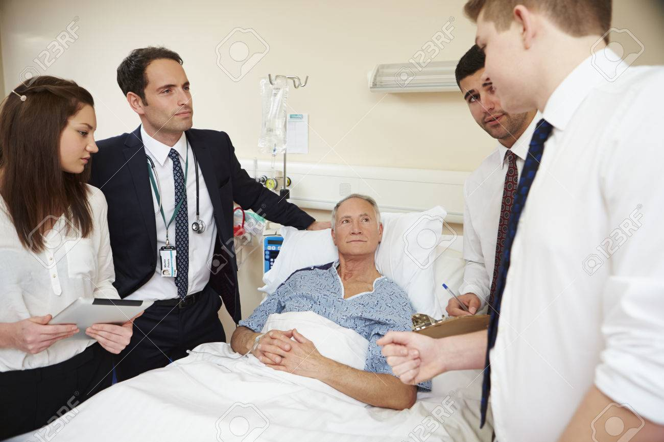 Medical Staff On Rounds Standing By Male Patient's Bed Stock Photo - 42402556