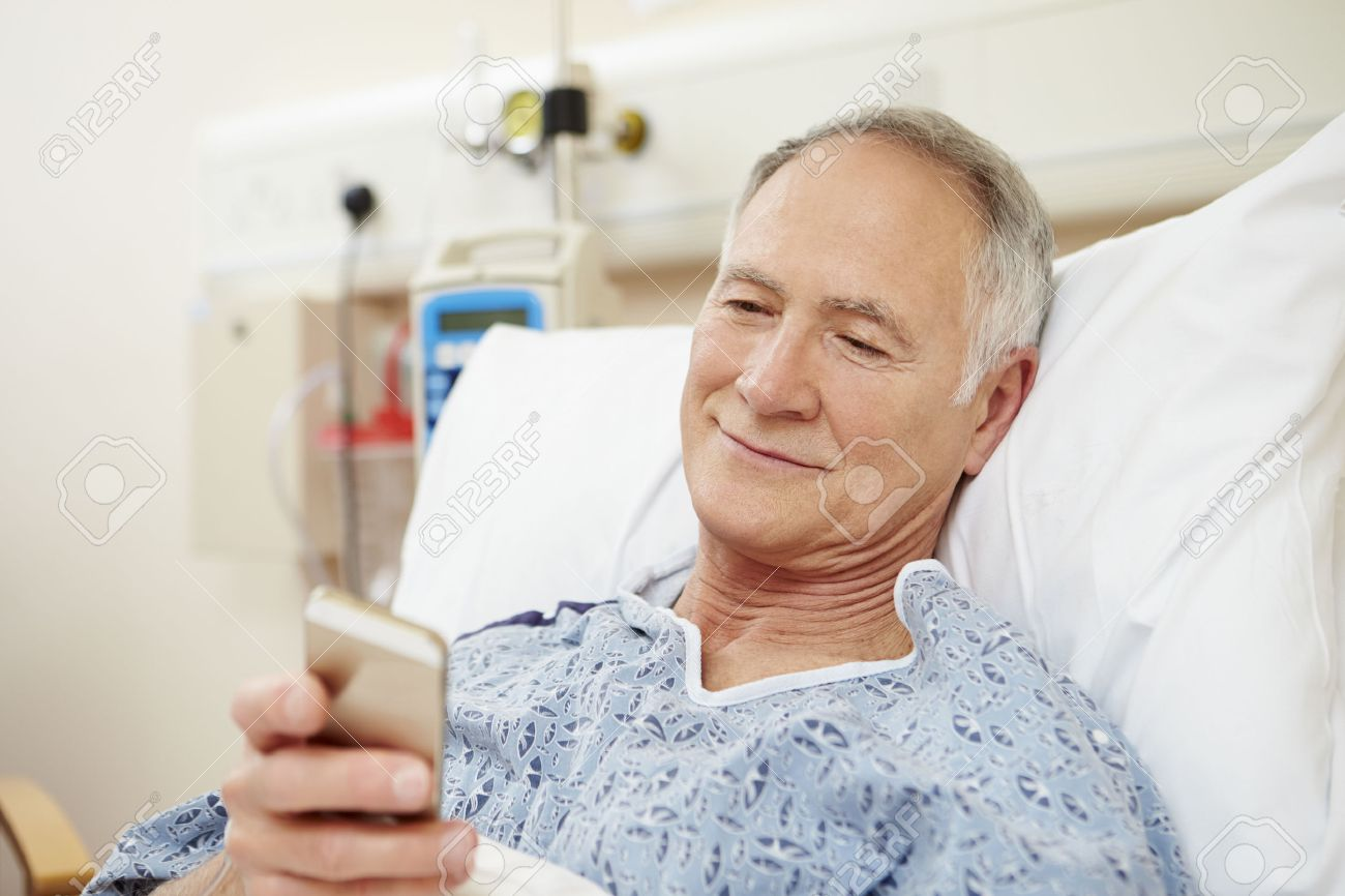 Senior Male Patient Using Mobile Phone In Hospital Bed Stock Photo - 42402583