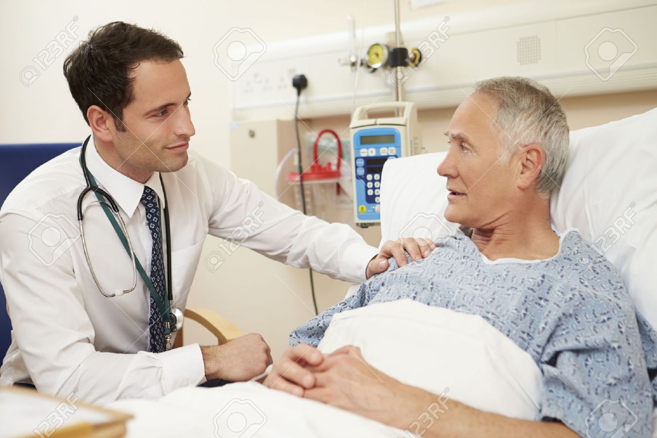 Doctor Sitting By Male Patient's Bed In Hospital Stock Photo - 42402717
