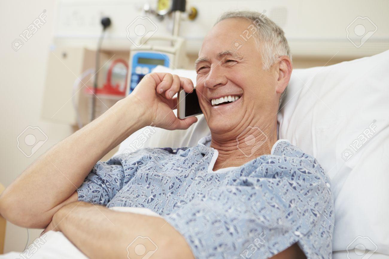Patient Homme senior utilisant un téléphone portable En lit d'hôpital Banque d'images - 42402747