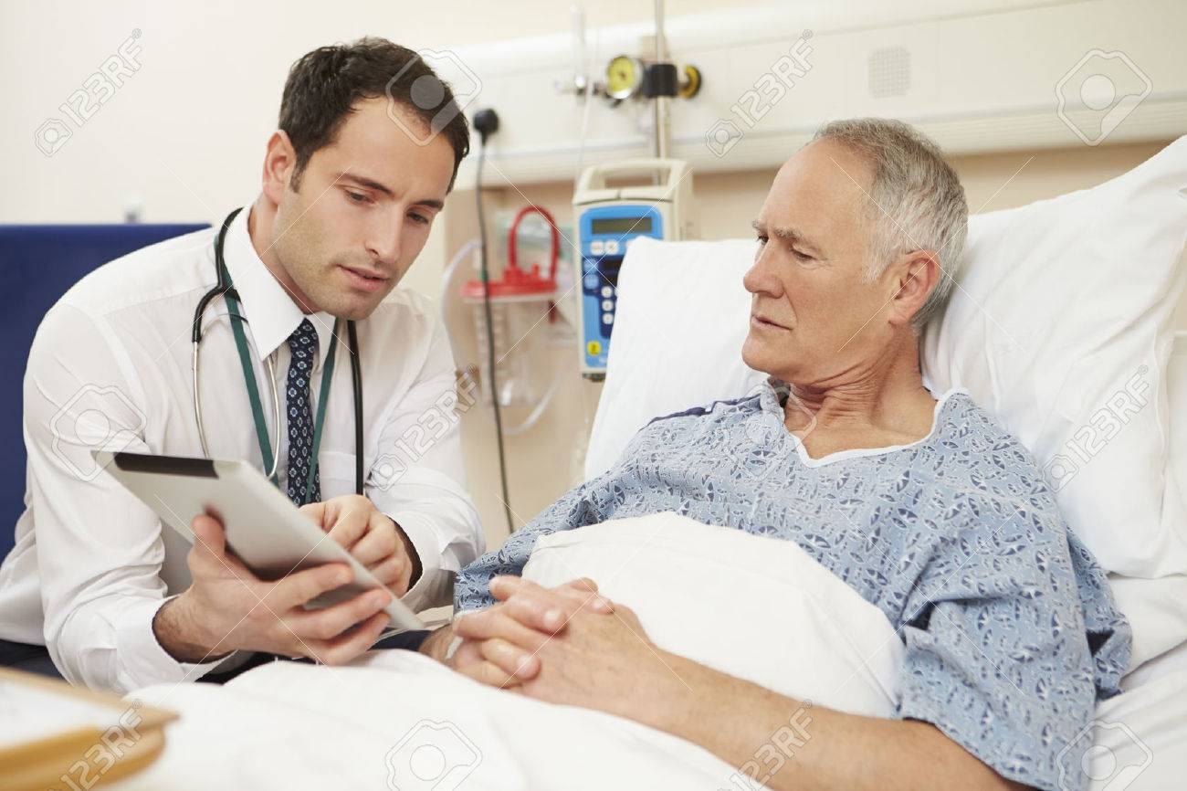 Doctor Sitting By Male Patient's Bed Using Digital Tablet Stock Photo - 42402908