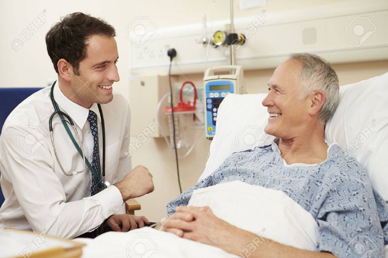 Doctor Sitting By Male Patient's Bed In Hospital Stock Photo - 42402984