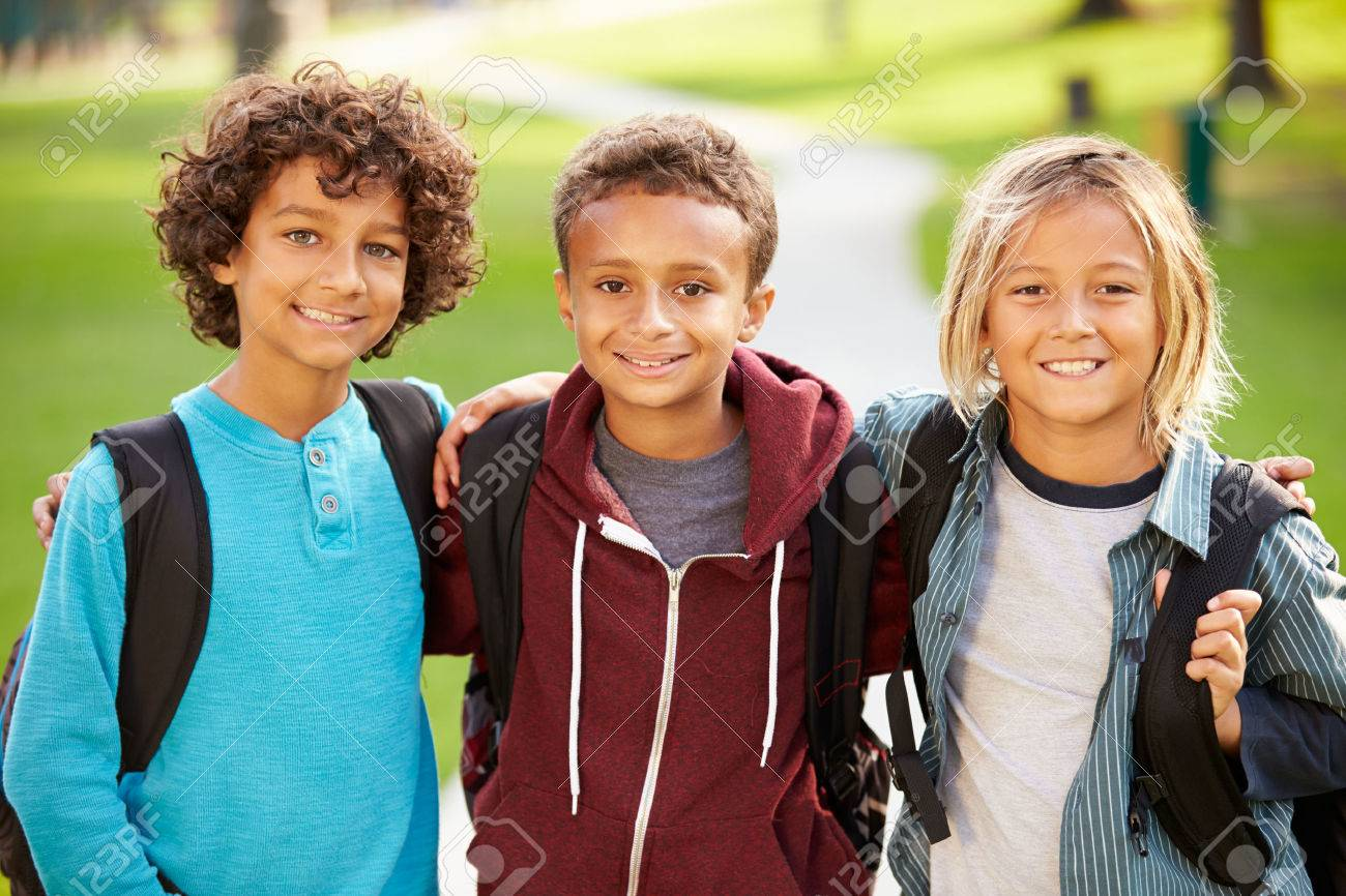 group of young boys hanging out in park together stock photo