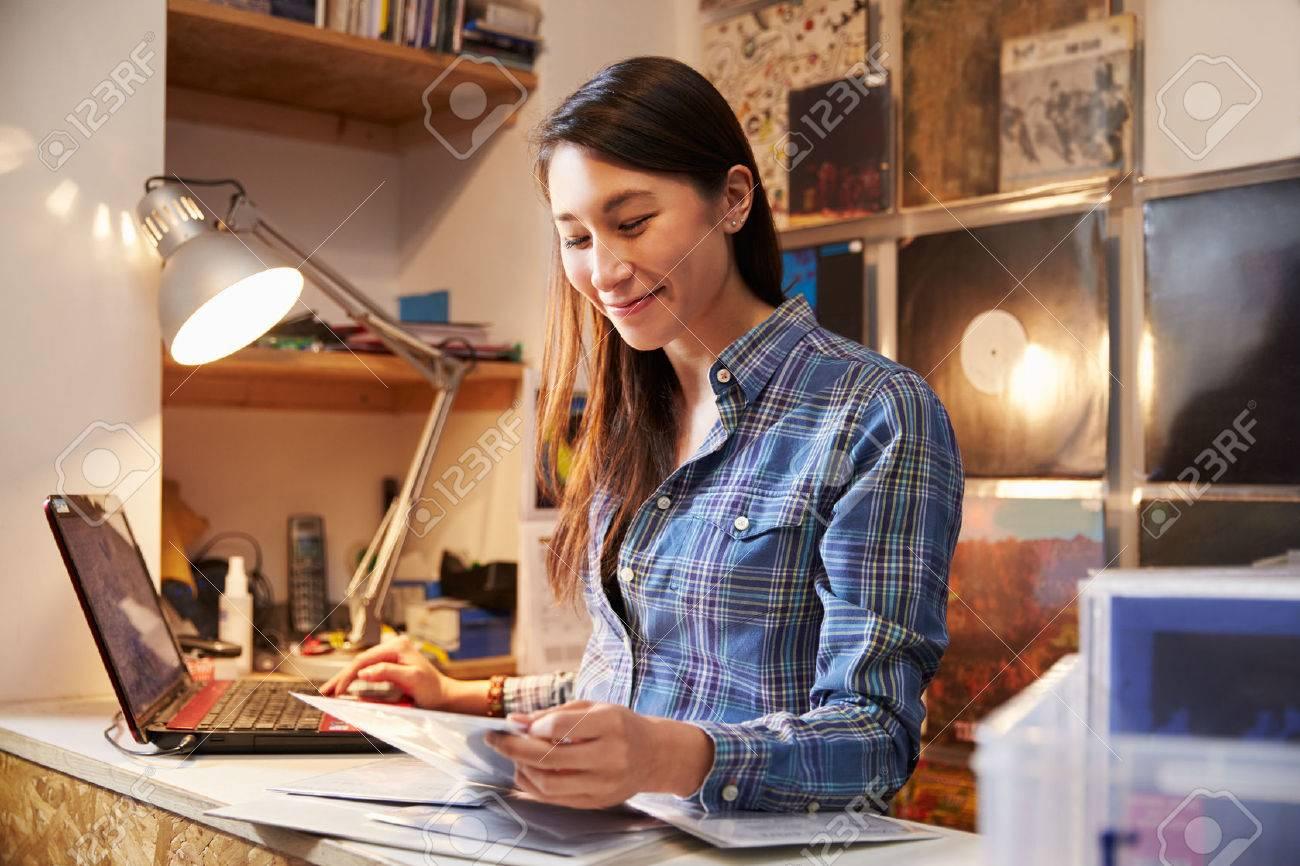 Jeune femme travaillant derrière le comptoir d'un magasin de disques Banque d'images - 43749282