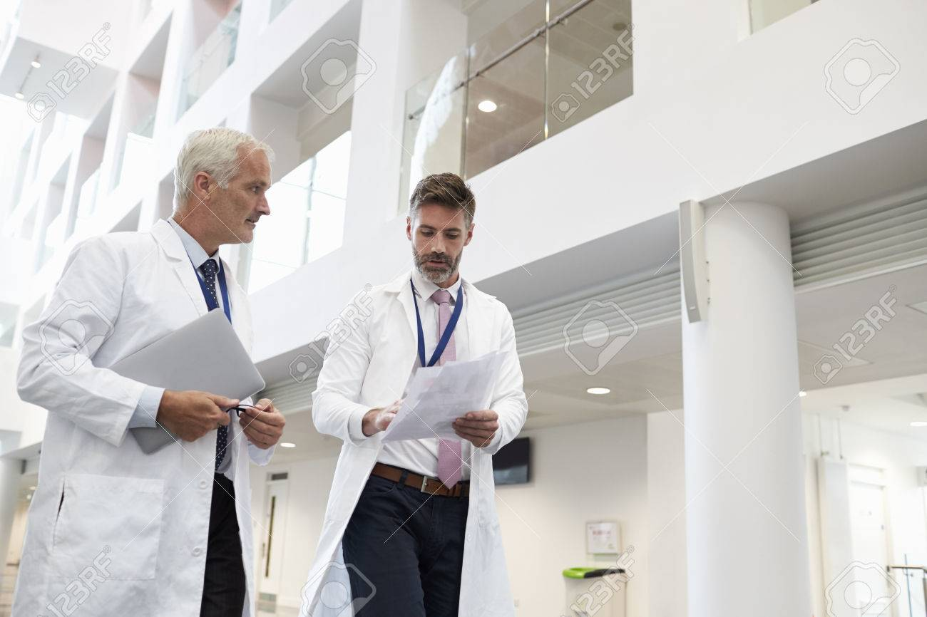 Two Doctors Talking As They Walk Through Modern Hospital Stock Photo - 71258973