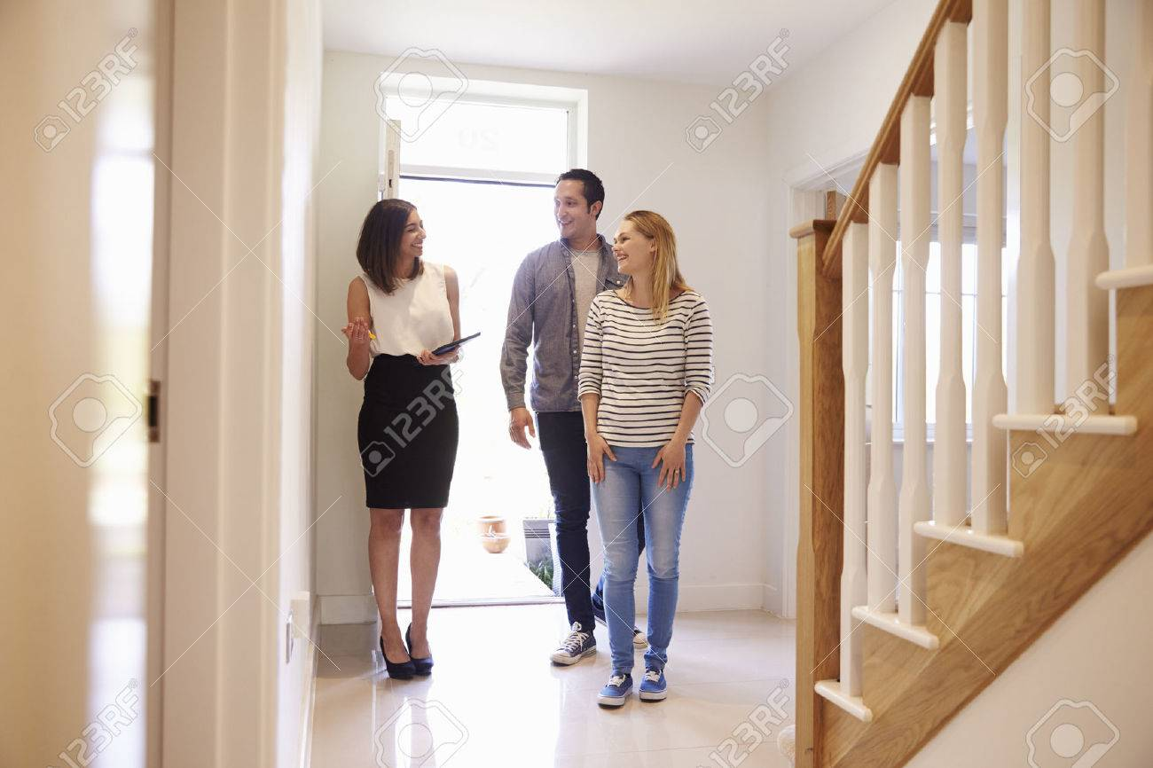 Realtor Showing Young Couple Around Property For Sale Stock Photo - 71259197