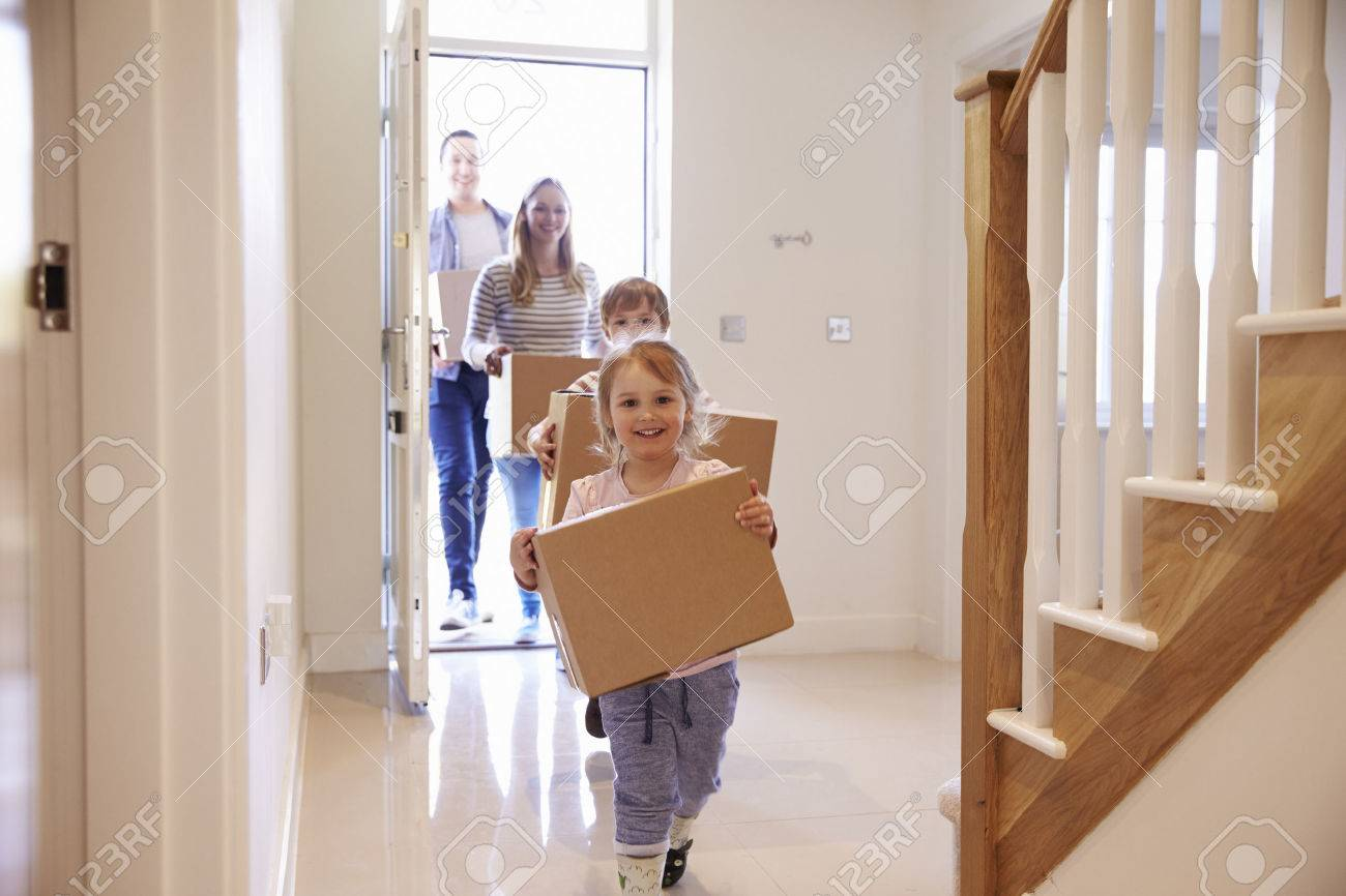 Family Carrying Boxes Into New Home On Moving Day Standard-Bild - 71259298