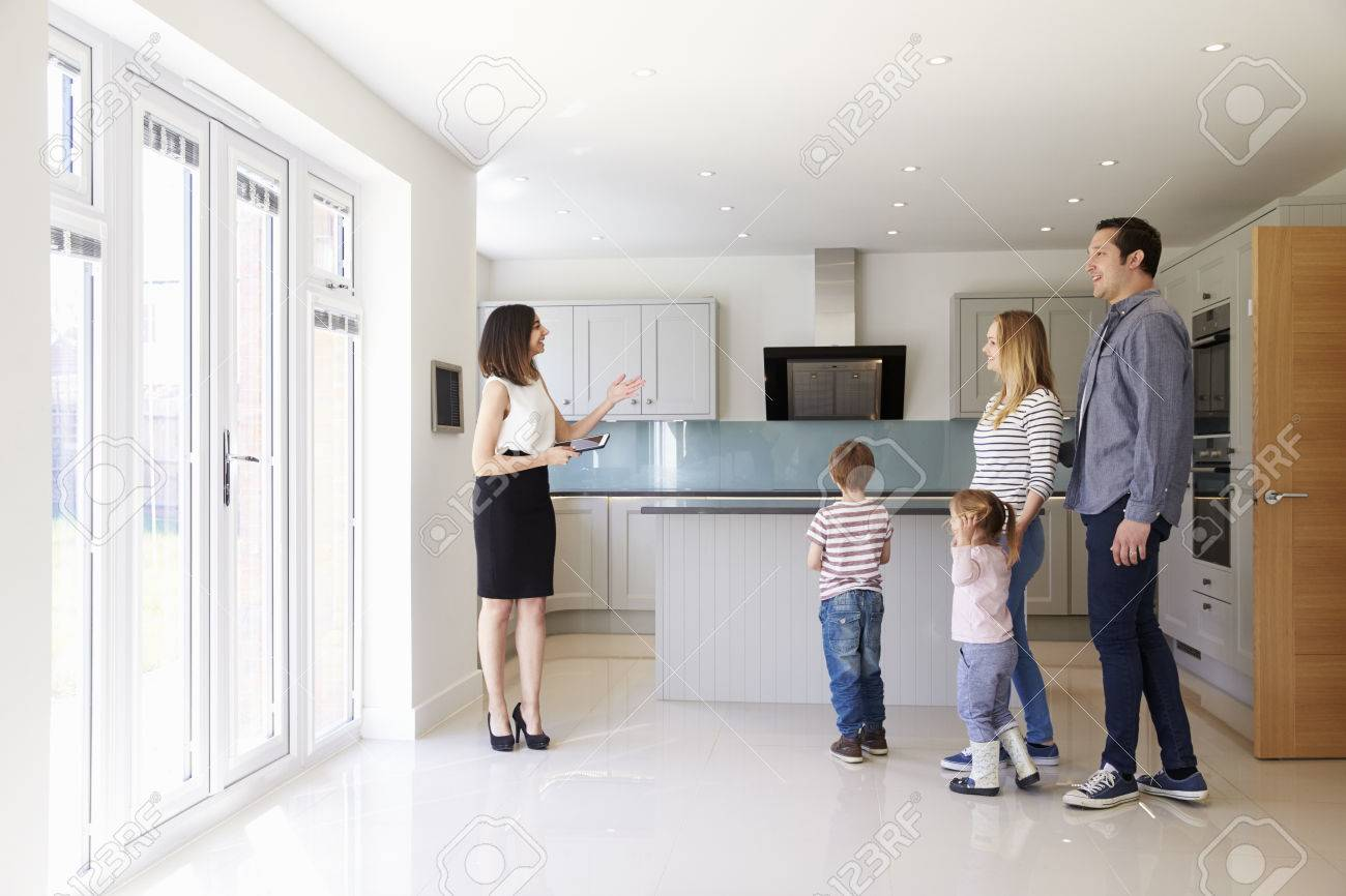 Realtor Showing Young Family Around Property For Sale Banque d'images - 71259082