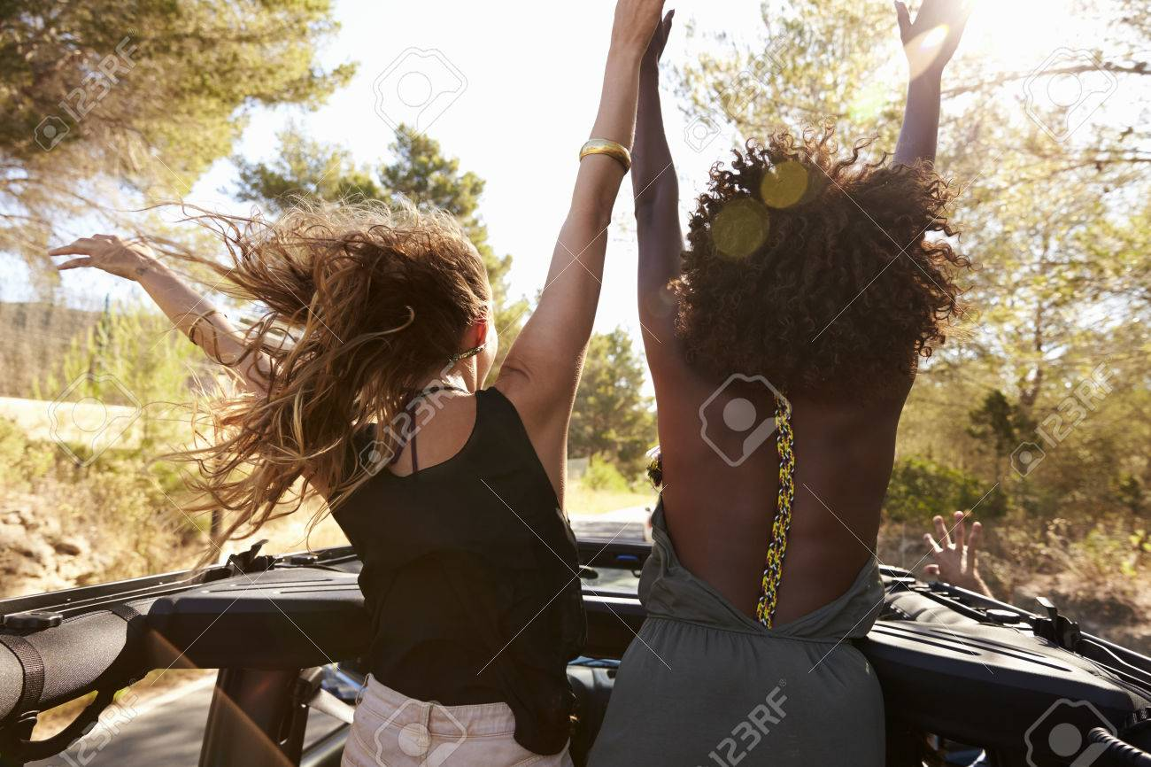 Two excited women stand in the back of open car, back view - 71304753