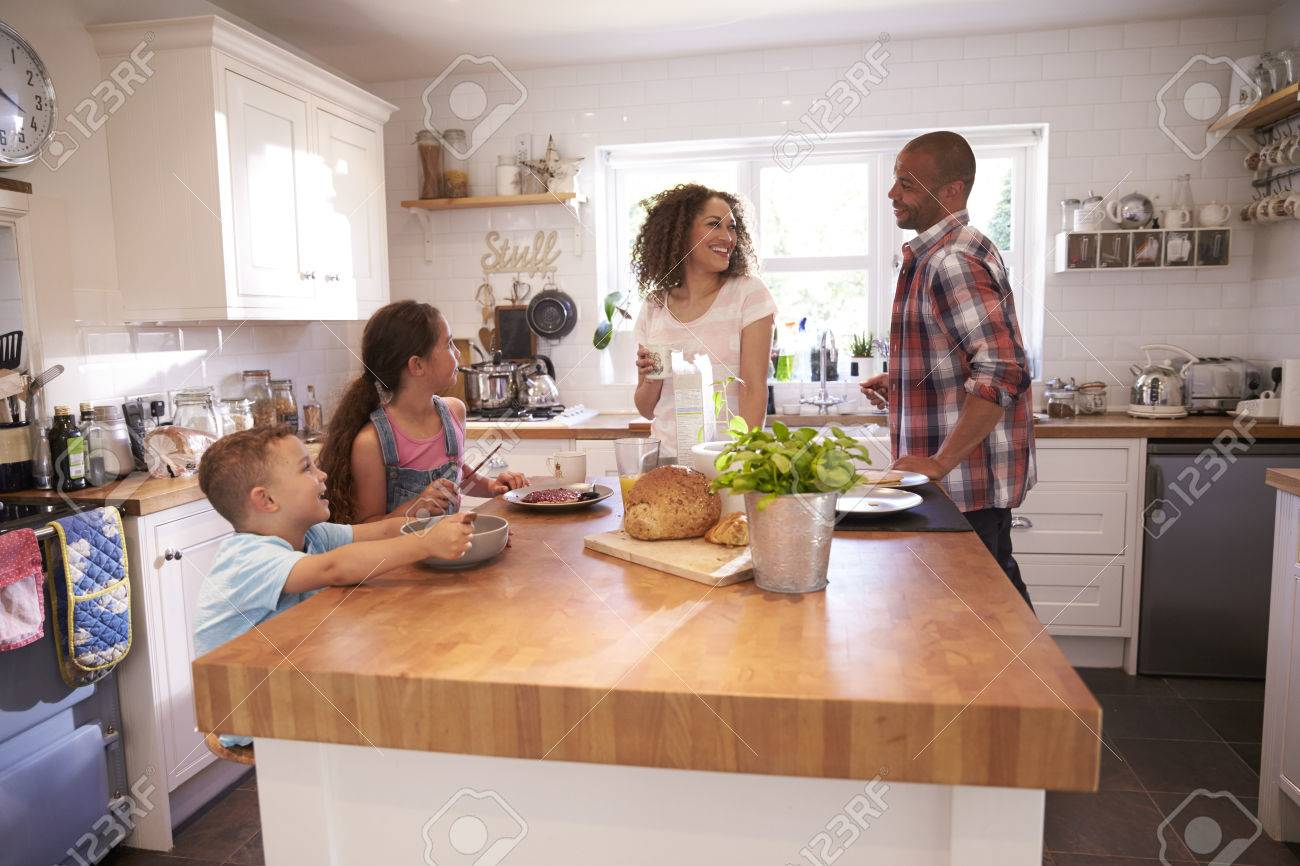 Family At Home Eating Breakfast In Kitchen Together Standard-Bild - 71214419