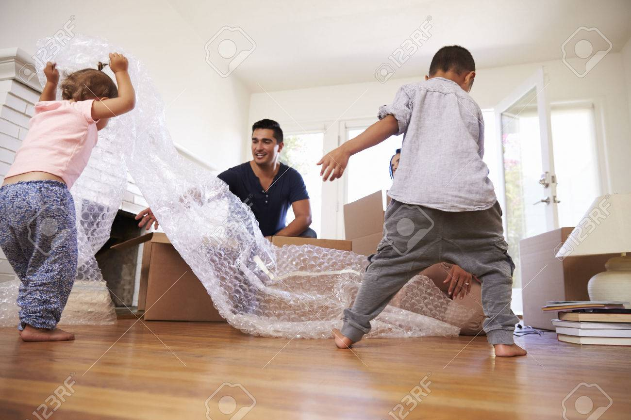 Family Unpacking Boxes In New Home On Moving Day Standard-Bild - 71266738