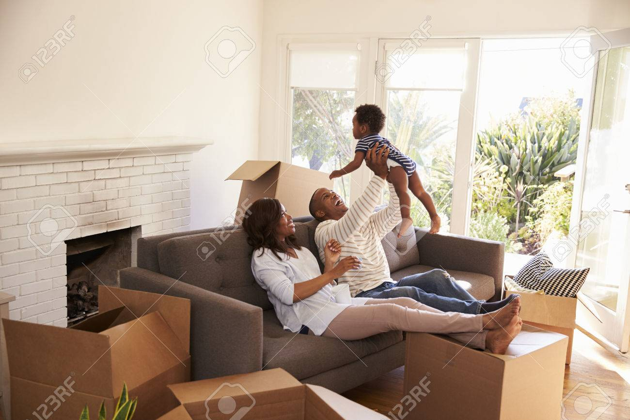 Parents Take A Break On Sofa With Son On Moving Day Banque d'images - 71270077