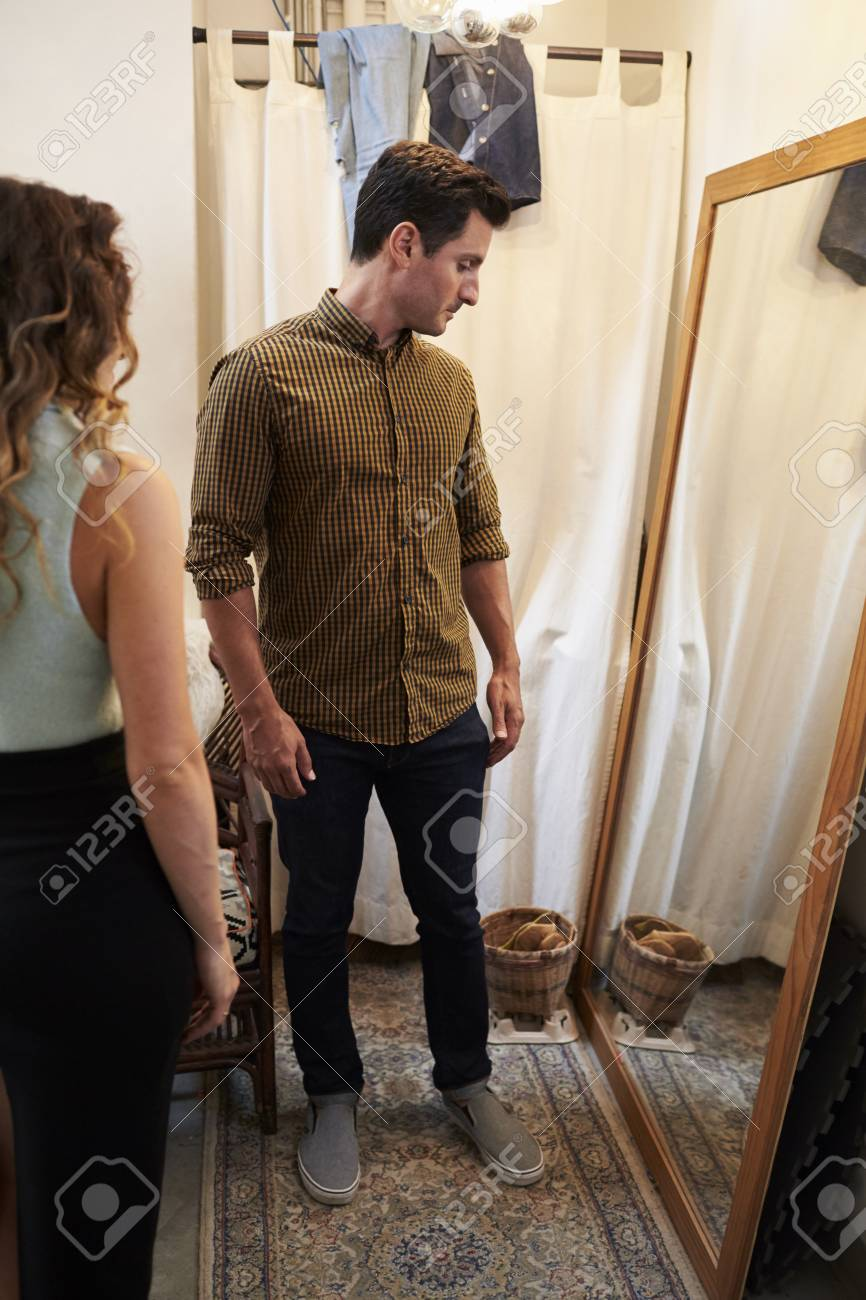 ce9e13d7ce2c Banque d images - Partner et l homme à essayer des vêtements dans le  vestiaire, vertical