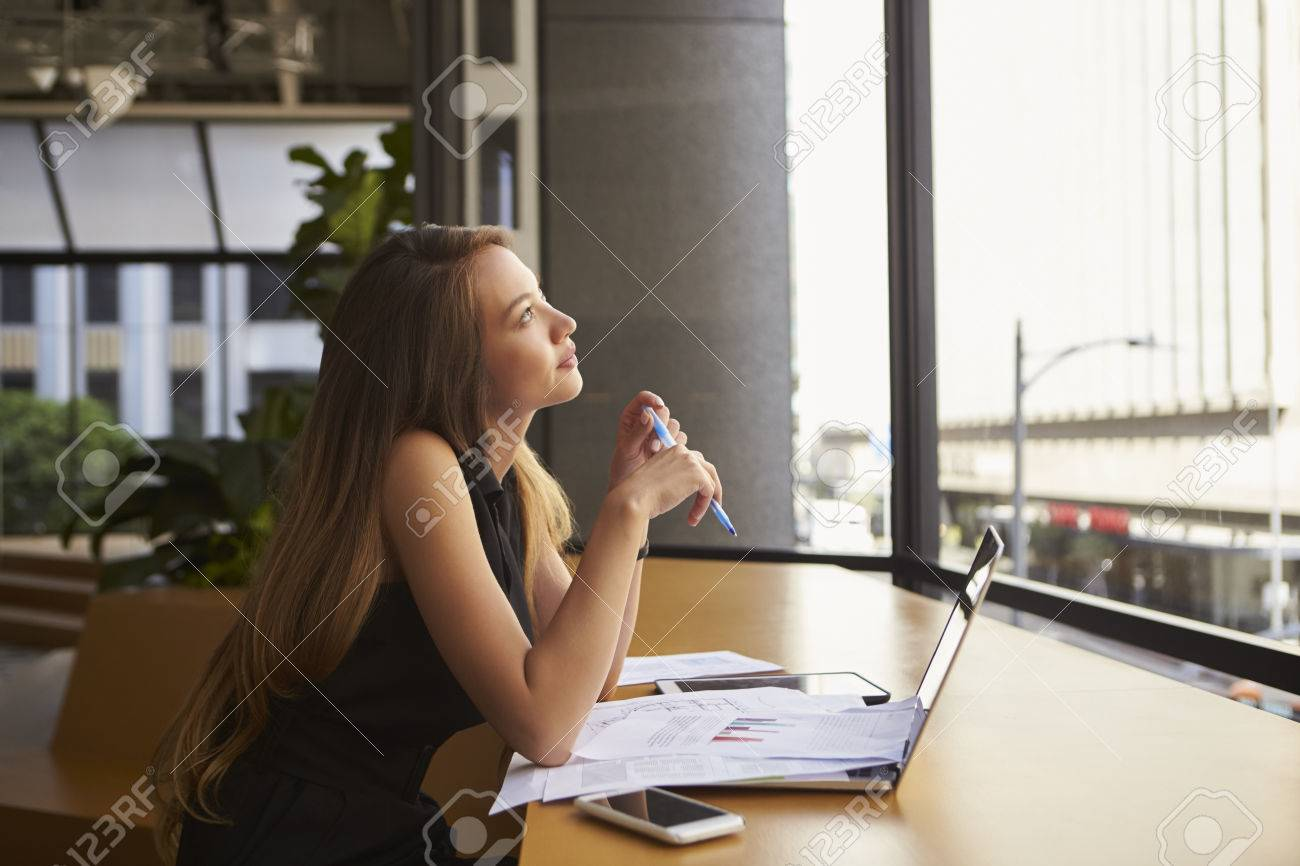 Businesswoman working in an office looking out of the window Standard-Bild - 71279976