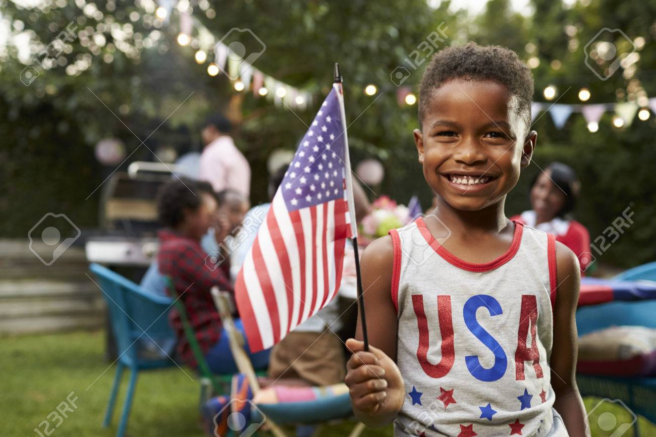 Young black boy holding flag at 4th July family garden party Standard-Bild - 71352995
