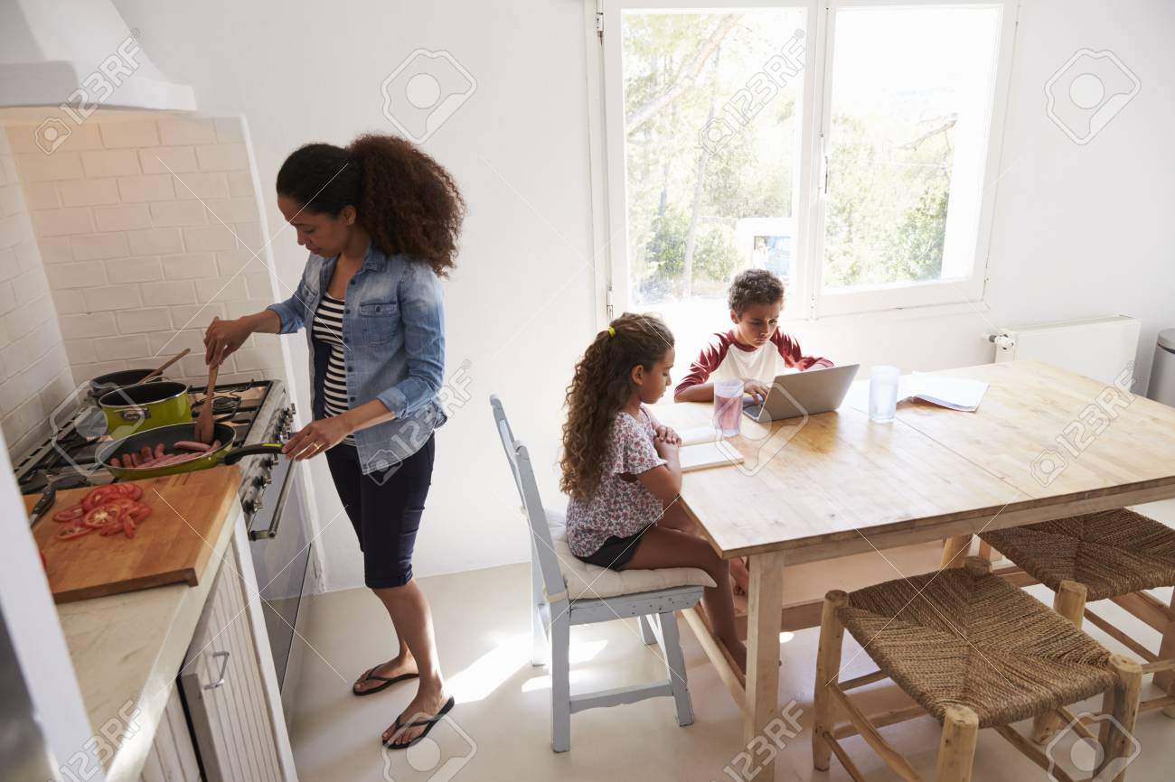 Mamá cocinando mientras los niños trabajan en la mesa de la cocina, vista  elevada
