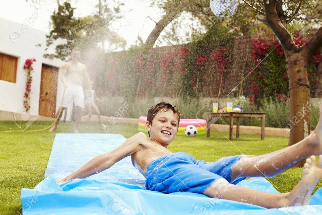Vater Und Sohn Die Spaß Auf Wasserrutsche Im Garten Lizenzfreie