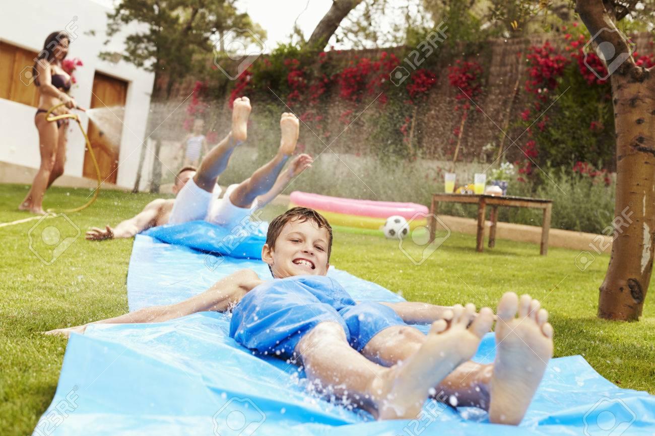 Familien Spaß Auf Wasserrutsche Im Garten Having Lizenzfreie Fotos
