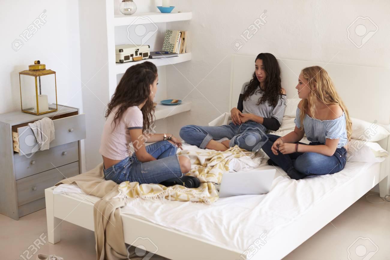 Drei Teenager Madchen Sitzen Auf Dem Bett Mit Laptop Sprechen