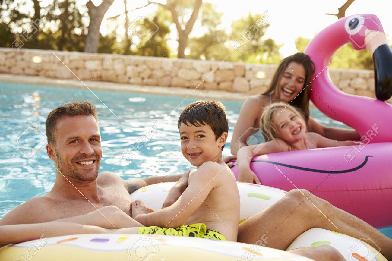 Family On Vacation On Inflatables In Outdoor Swimming Pool Stock Photo - 71403405