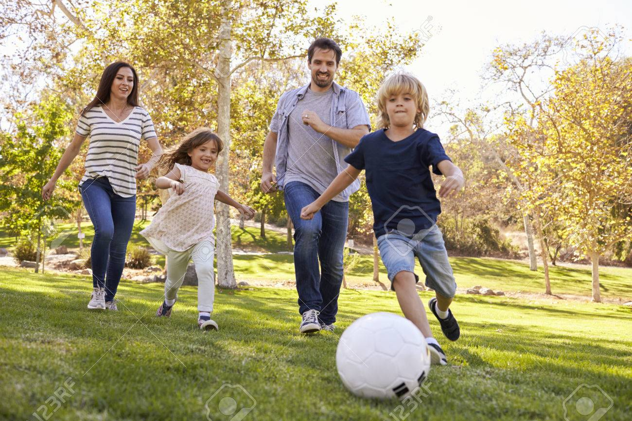 Family Playing Soccer In Park Together Stock Photo Picture And