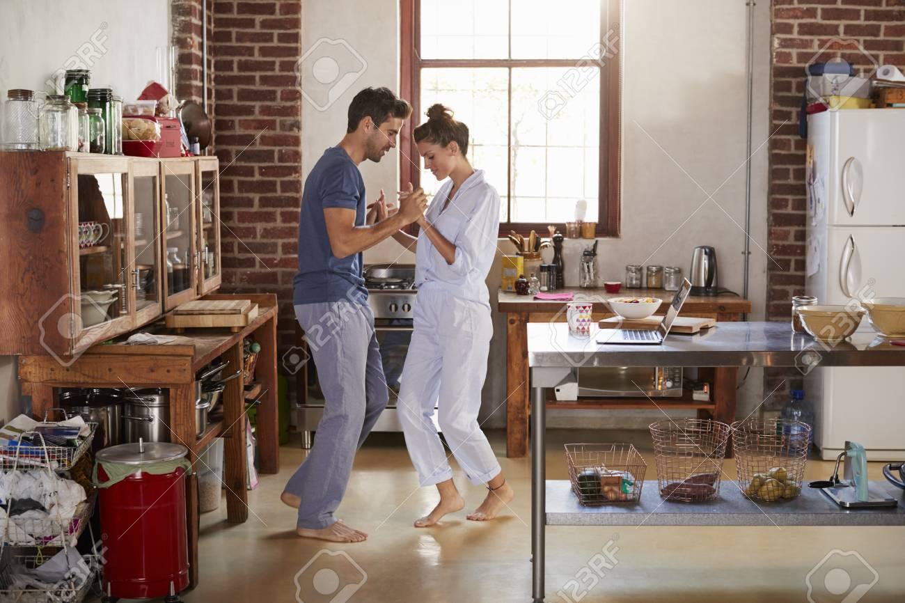 Hispanic Couple In Pyjamas Dancing In Kitchen, Full Length Stock Photo    79573562