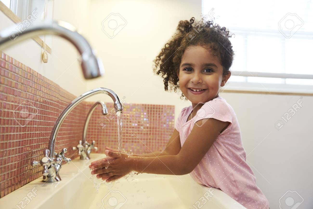 Female Pupil At Montessori School Washing Hands In Washroom - 79574129
