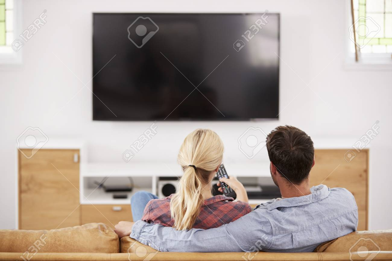 Rear View Of Couple Watching Television Together - 86206660