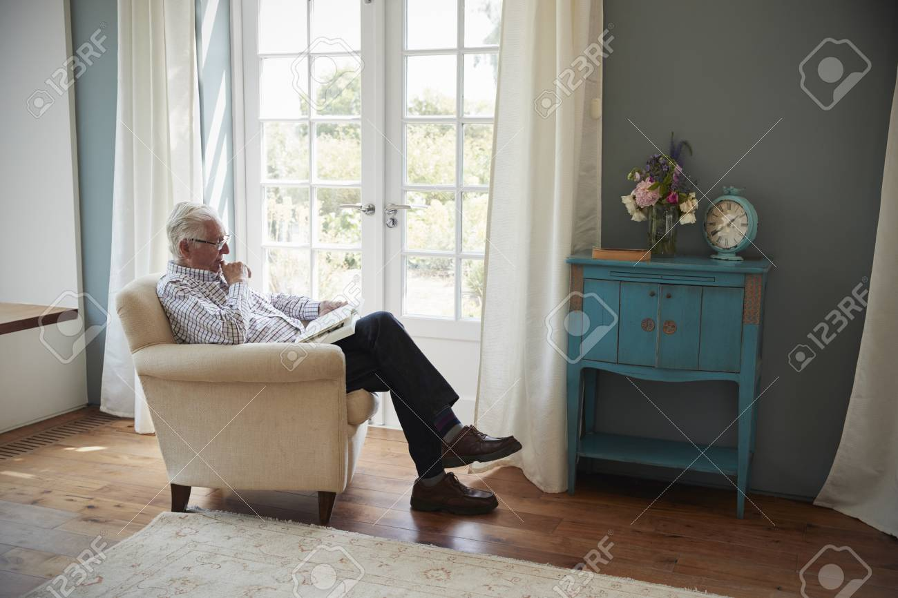 photo senior man sitting in an armchair reading a book at home