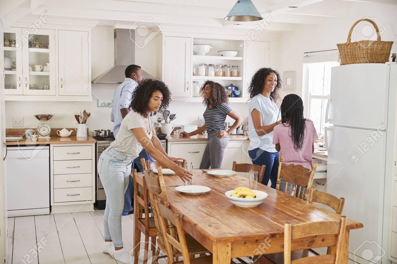 Familia con hijas de bebé poniendo mesa para alimentos en la cocina