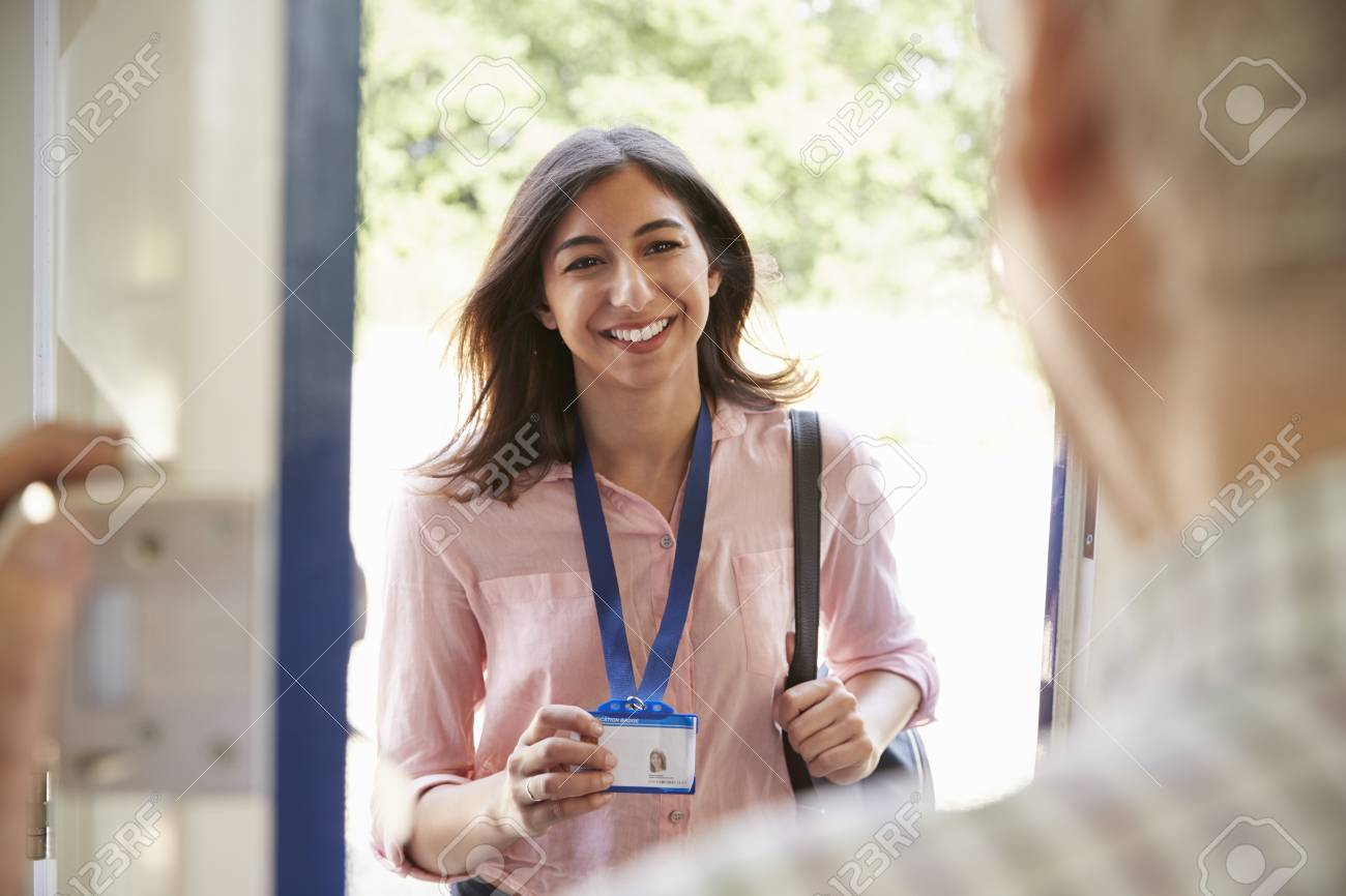 Senior man opening front door to young woman showing ID card - 88062565
