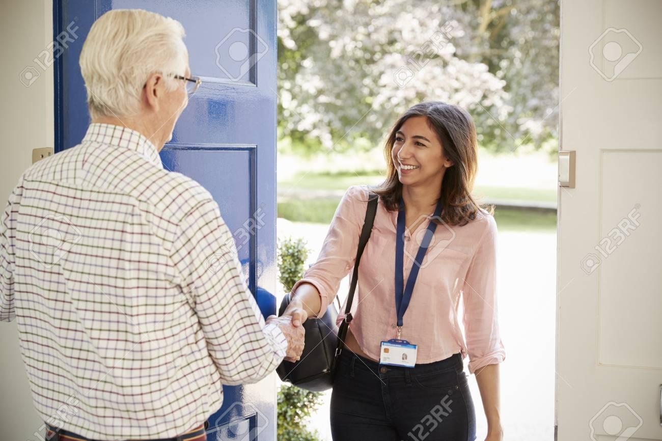 Senior homme saluant une jeune femme faisant une visite à domicile