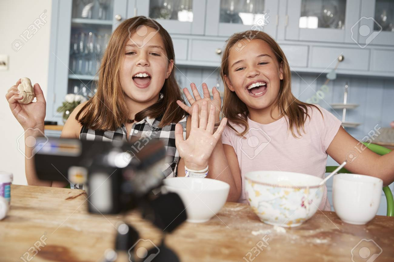 Stock Photo - Two pre-teen girls video blogging in the kitchen waving to  camera