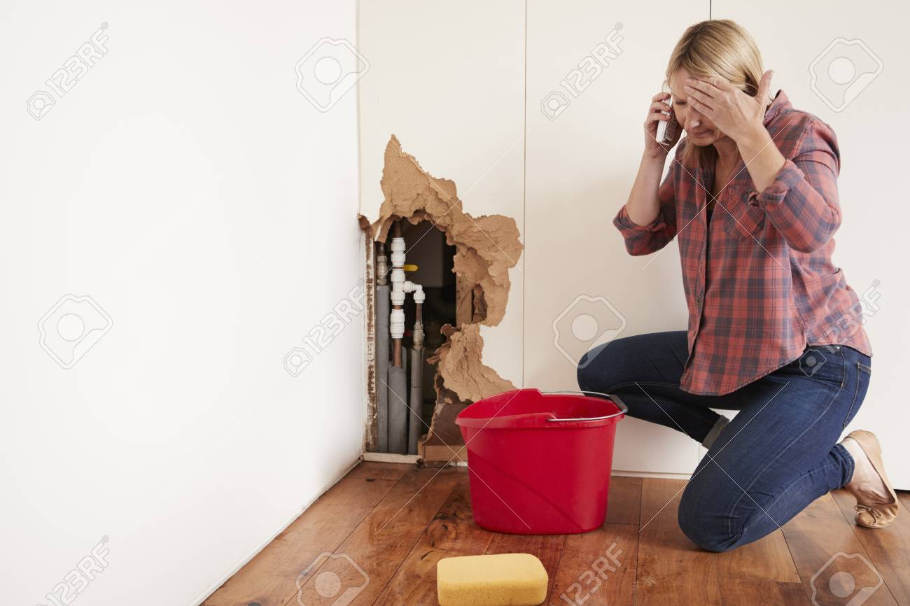 Middle aged woman with a burst water pipe phoning for help - 91579671