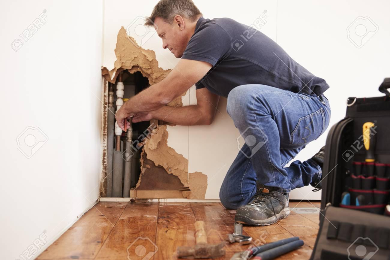 Middle aged man repairing burst water pipe - 91650568