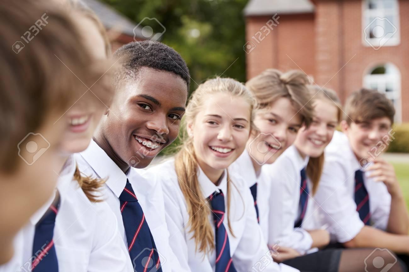 Group Of Teenage Students In Uniform Outside School Buildings - 91650586