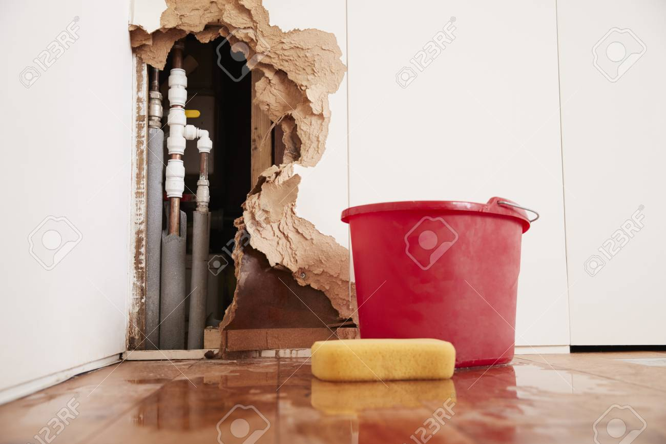 Damaged wall, exposed burst water pipes, sponge and bucket - 91652607