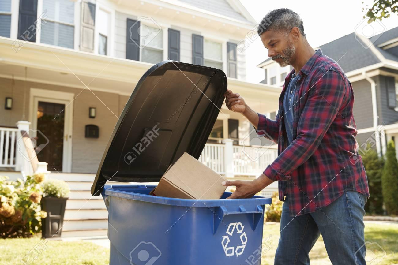 Man Filling Recycling Bin On Suburban Street - 93401657