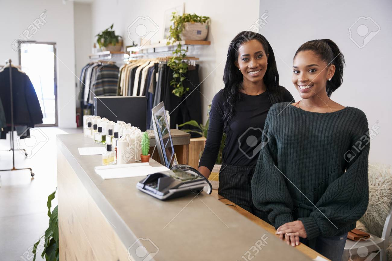Two women smiling behind the counter in clothing store - 93402608