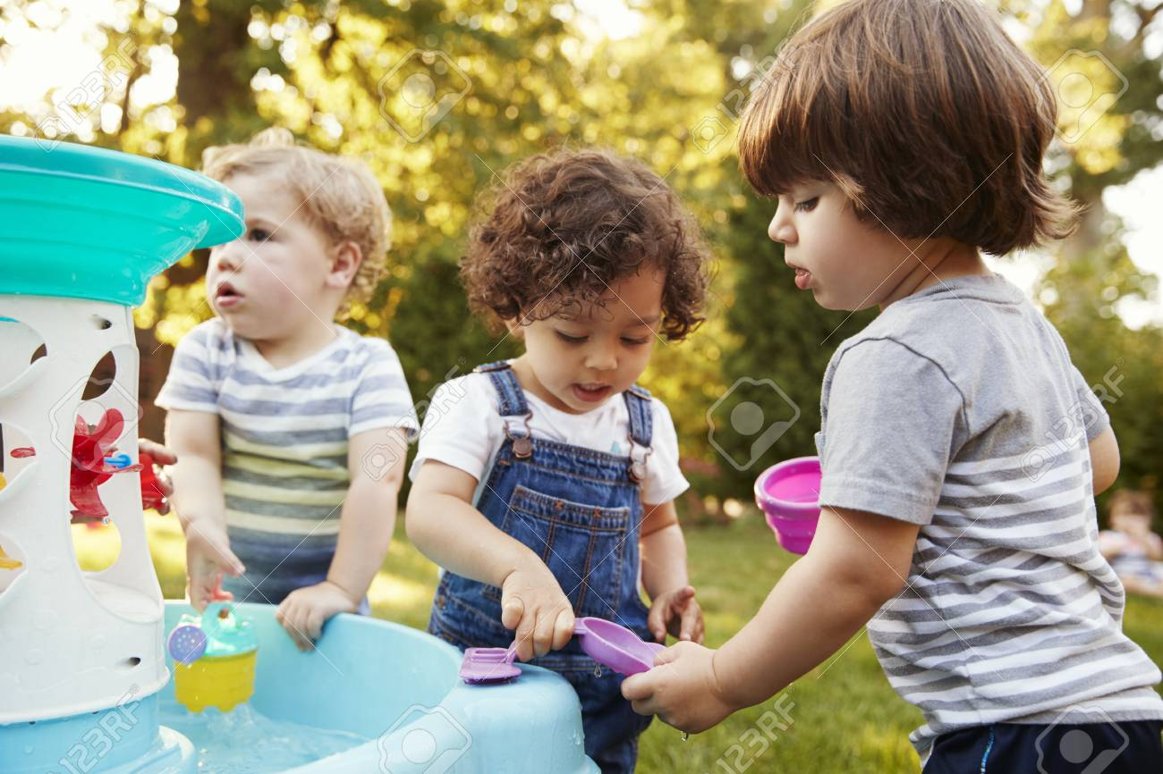 Group Of Young Children Playing With Water Table In Garden - 93397374