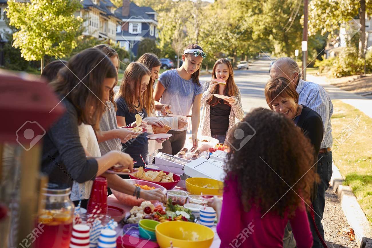 Neighbours standing around a table at a block party - 93401797