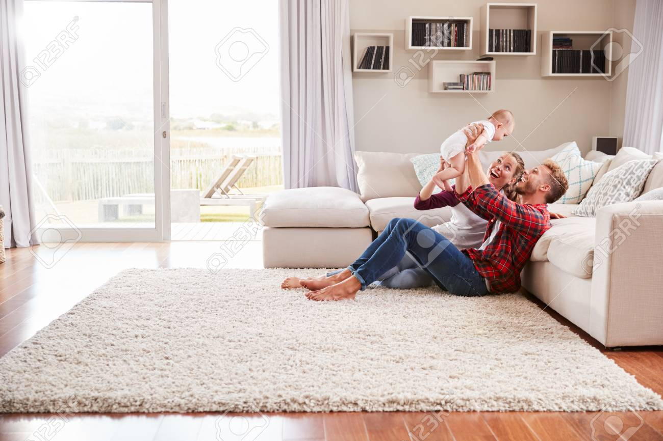 Young white couple play with their toddler in sitting room - 99774491