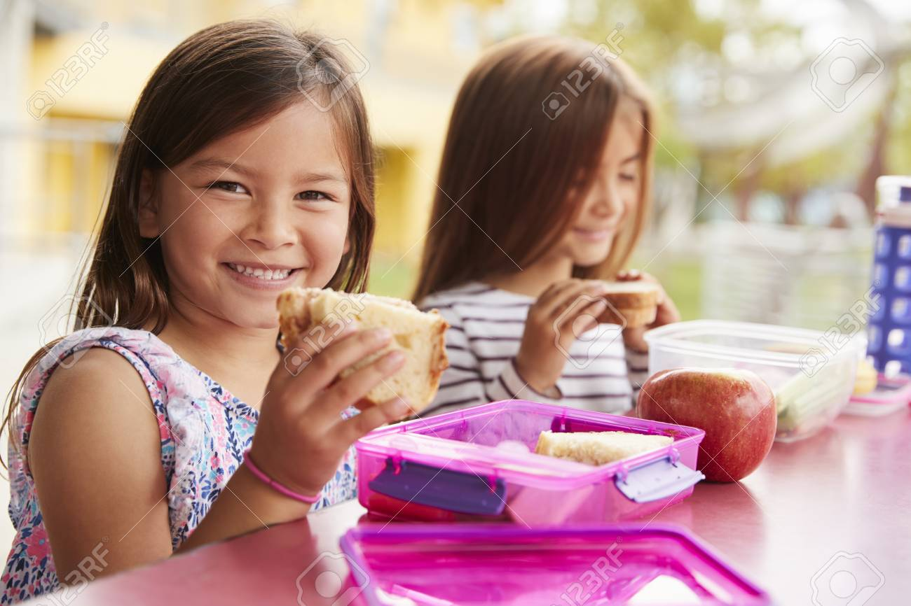 Young schoolgirls holding sandwiches at school lunch table - 109005766