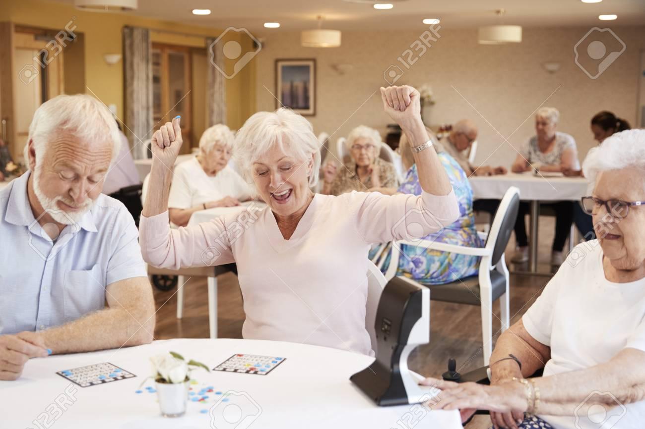 Senior Woman Winning Game Of Bingo In Retirement Home - 109543375