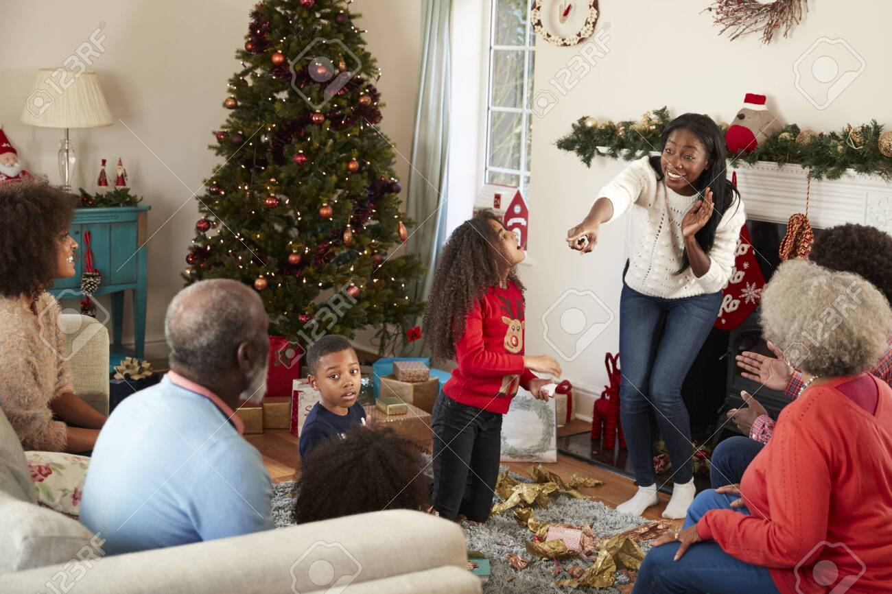 Multi Generation Family Playing Game Of Charades As They Celebrate Christmas At Home Together - 115490446
