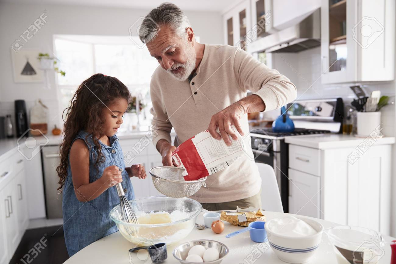 Young girl preparing cake mixture with her grandfather at the kitchen table, close up - 115390747